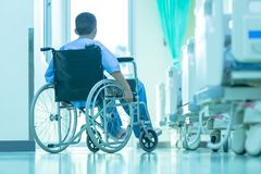 Asian disabled man is sitting in a wheelchair. He holds his hand royalty free stock photo