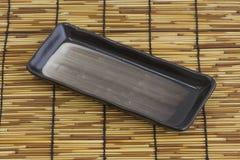 Asian dish. A painted asian rectangular dish on bamboo mattress stock photography