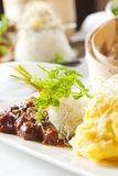 Asian dish with beef, noodles and vegetables. On table with assorted dishes stock image