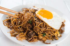 Asian dish Char Kuey Teow. Close-up stir fried char kuey teow with chopstick over wooden background stock images