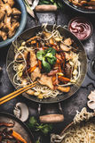 Asian dish with chicken vegetables noodle stir-fry in little wok with chopstick and cooking ingredients. Top view stock photos