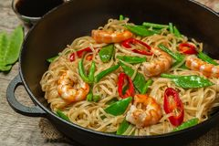 Asian dish of fried rice noodles with shrimp and vegetables. Asian dish of fried rice noodles with shrimp,vegetables and hot pepper with soy sauce royalty free stock image