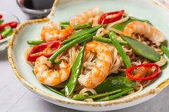 Asian dish of fried rice noodles with shrimp and vegetables. Asian dish of fried rice noodles with shrimp,vegetables and hot pepper with soy sauce stock photo
