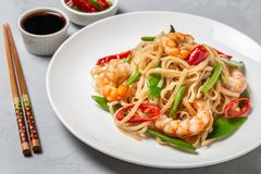 Asian dish of fried rice noodles with shrimp and vegetables. Asian dish of fried rice noodles with shrimp,vegetables and hot pepper with soy sauce royalty free stock photography