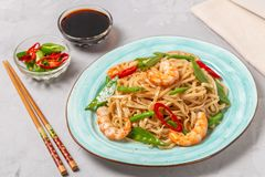 Asian dish of fried rice noodles with shrimp and vegetables. Asian dish of fried rice noodles with shrimp,vegetables and hot pepper with soy sauce stock photography