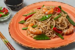 Asian dish of fried rice noodles with shrimp and vegetables royalty free stock image