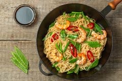 Asian dish of fried rice noodles with shrimp and vegetables. The view from the top. Copy-space. royalty free stock photo