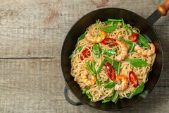 Asian dish of fried rice noodles with shrimp and vegetables. The view from the top. Copy-space. stock photos