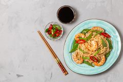 Asian dish of fried rice noodles with shrimp and vegetables. The view from the top. Copy-space. stock photography