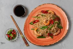 Asian dish of fried rice noodles with shrimp and vegetables. The view from the top. Copy-space. stock photo
