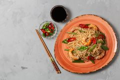 Asian dish of fried rice noodles with shrimp and vegetables. The view from the top. Copy-space. royalty free stock image