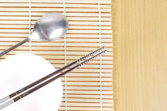 Asian dish place setting on bamboo mat Royalty Free Stock Photography