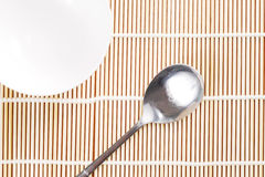 Asian dish place setting on bamboo mat, Korean style. Asian spoon and chopsticks setting on bamboo mat Royalty Free Stock Images