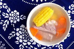 Asian dish, Pork ribs, corn & carrot soup. A photograph showing a home cooked dish of asian style, pork rib soup with corn cobs and pieces of carrots. Delicious stock image