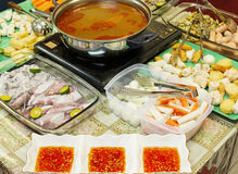 Asian dishes - tomyam steamboat. Set with various ingredients and spicy dipping sauce royalty free stock photography