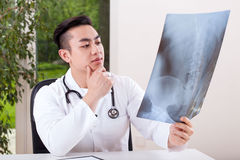 Asian doctor analysing X-ray Stock Photography