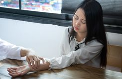 Asian doctor is checking patience`s pulse by fingers. /Girls feel bad Stock Images