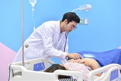 Asian doctor examining pregnant woman with stethoscope. Asian doctor examining pregnant women with stethoscope at maternity ward Royalty Free Stock Photography