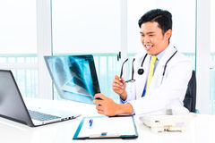 Asian doctor examining x-ray picture in practise Royalty Free Stock Images