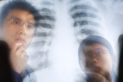 Asian doctor examining xray negative Stock Photography