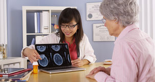 Asian doctor explaining brain scans to elderly patient Royalty Free Stock Images