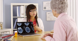 Asian doctor explaining brain scans to elderly patient Royalty Free Stock Photos