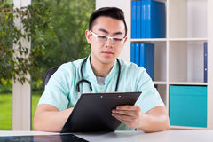 Asian doctor filling documents Royalty Free Stock Photography