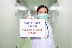 Asian doctor at hospital wear medical masks, holding paper with text I STAY AT WORK FOR YOU, YOU STAY AT HOME FOR US. stay at home