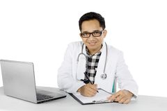 Asian doctor with laptop and clipboard on studio. Asian male doctor smiling at the camera while working with a laptop and clipboard, isolated on white background Royalty Free Stock Image