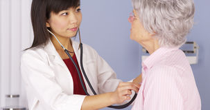 Asian doctor listening to elderly patient's heart Stock Images