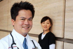 Asian doctor with nurse in background Stock Images