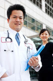 Asian doctor with nurse in background Royalty Free Stock Photo