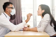 Doctor check Tonsil and sore throat. Asian doctor or physician check Tonsil and sore throat of beautiful women while the girl open her mouth at hospital stock image