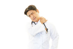 Asian doctor with shoulder pain. royalty free stock photos