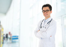 Asian doctor standing at hospital corridor Stock Image