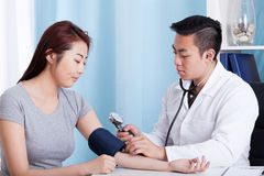 Asian doctor taking blood pressure of a patient Royalty Free Stock Images