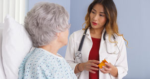 Asian doctor talking to elderly woman in bed about prescription medication stock images