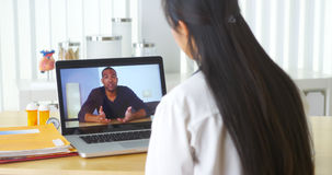 Asian doctor video chatting with African patient. In the office Royalty Free Stock Photo