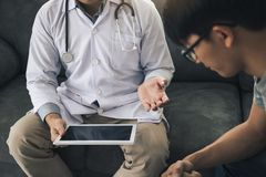 Asian doctor visited the patient at home while using the tablet explaining the patient condition and the treatment result.  stock image