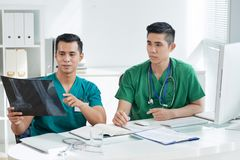 Asian doctors examining X-ray picture. Two Asian men in scrubs looking at bone X-ray picture while sitting at desk in hospital office stock image