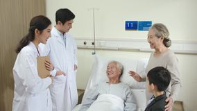 Asian doctors talking to senior patient and family members in hospital ward
