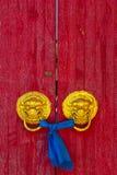 Asian door knobs. On a red door Stock Photo