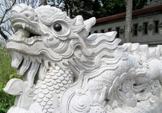 Asian dragon marble sculpture. At the mountain top, sculpture in buddhist pagoda.Beautiful fantastic dragon in the Buddhist temple, the green trees around Stock Photography
