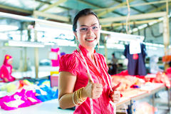 Asian dressmaker in a textile factory. Female Chinese asian dressmaker or designer standing proudly in a textile factory, it is her workplace stock photo