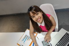 Asian dumple office girl with nice smile at workplace Royalty Free Stock Image