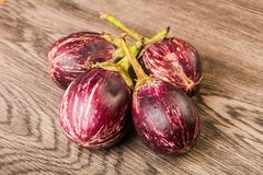 Asian eggplant. Heap over the wooden background royalty free stock photography