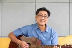 Free Asian Elder Man Enjoy Playing Guitar At The Sofa Inside Of Well Interior Decoration House. Active Senior Lifestyle After Stock Images - 215712304