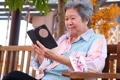 Elder woman holding mobile phone in garden. elderly female texti royalty free stock photo