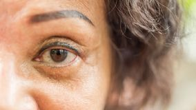 Asian elder women show her eyes and eyebrow tattoo. Asian elder woman 60s with black hair and wrinkled on face show her eyes and eyebrow tattoo before cornea royalty free stock image
