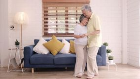 Asian elderly couple dancing together while listen to music in living room at home, sweet couple enjoy love moment.